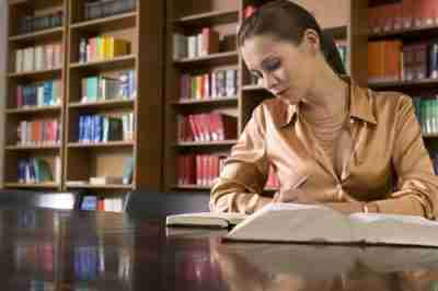 סטודנטית צעירה כותבת על שולחן בסיפרייה