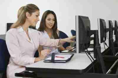 שתי נשות עסקים יושבות בכיתת מחשבים