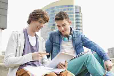 סטודנטים שמחים יושבים עם טאבלט